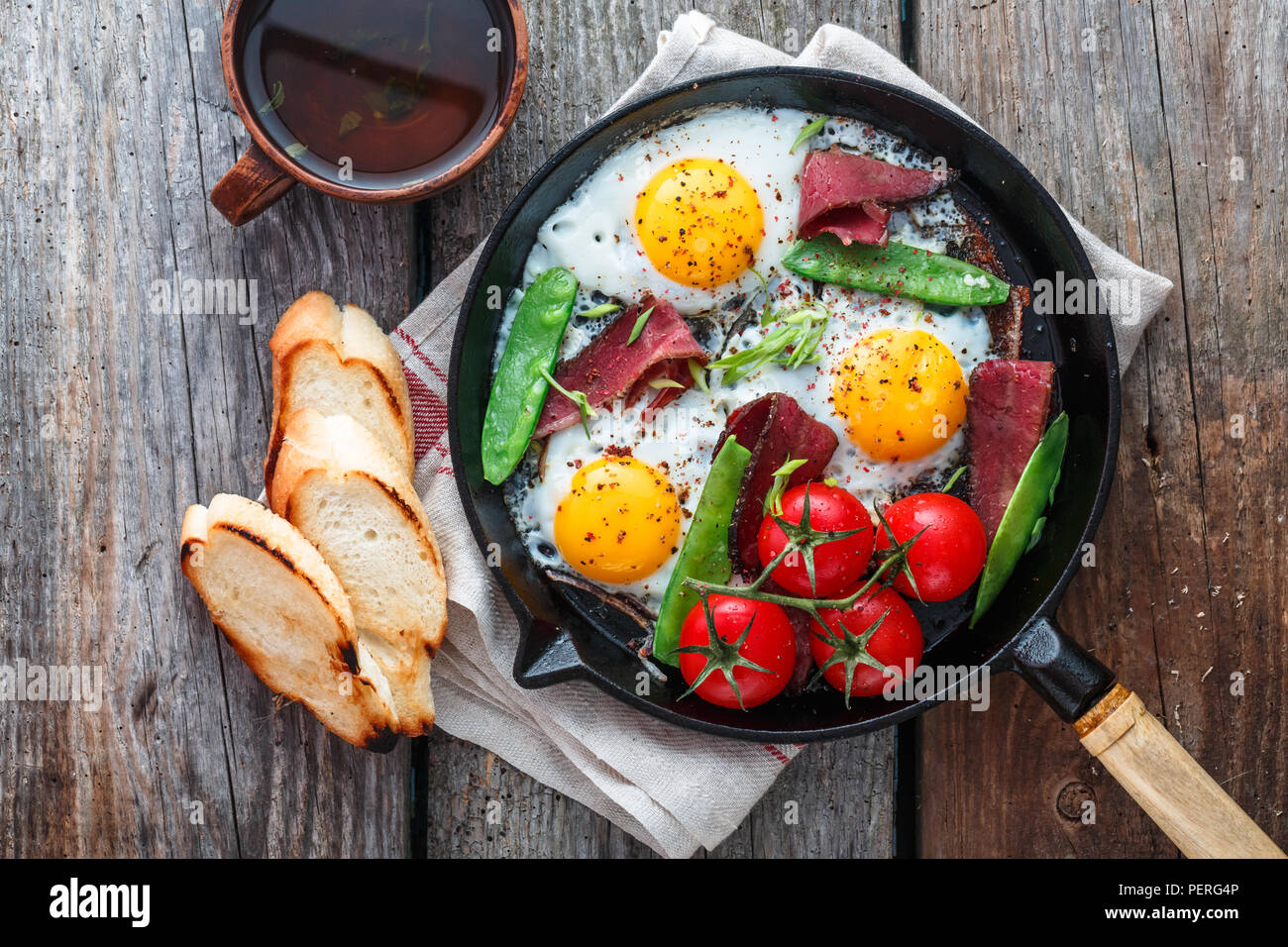 Fried eggs in a frying pan with cherry tomatoes, green peas and pastrami. Copyspace - Stock Image