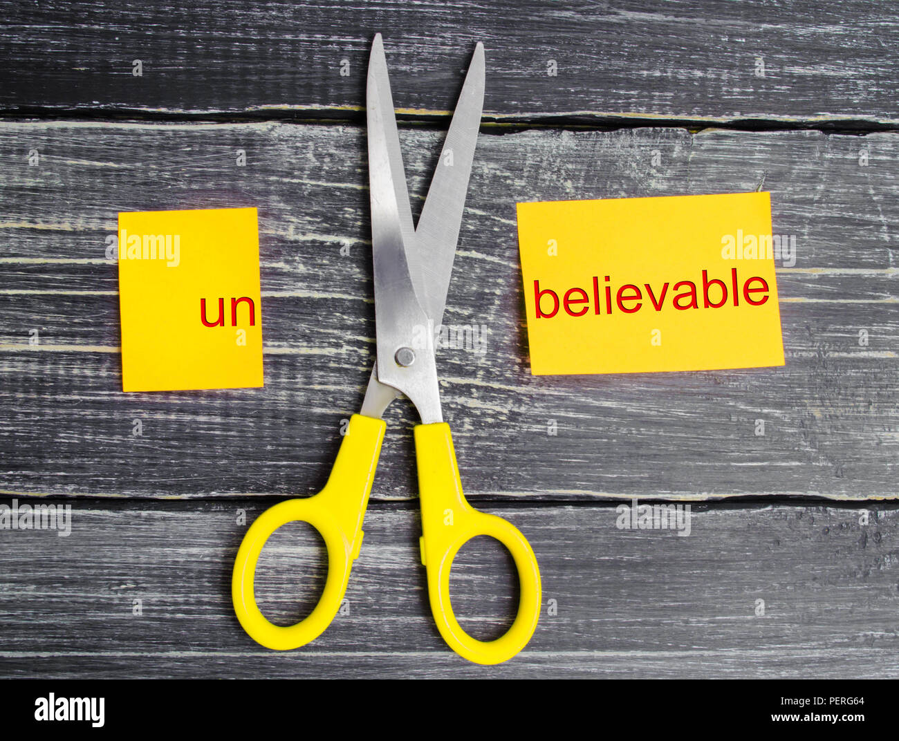 scissors cut the word unbelievable. concept believable. cuts the word 'un. 'I can, goal achievement, potential, overcoming - Stock Image