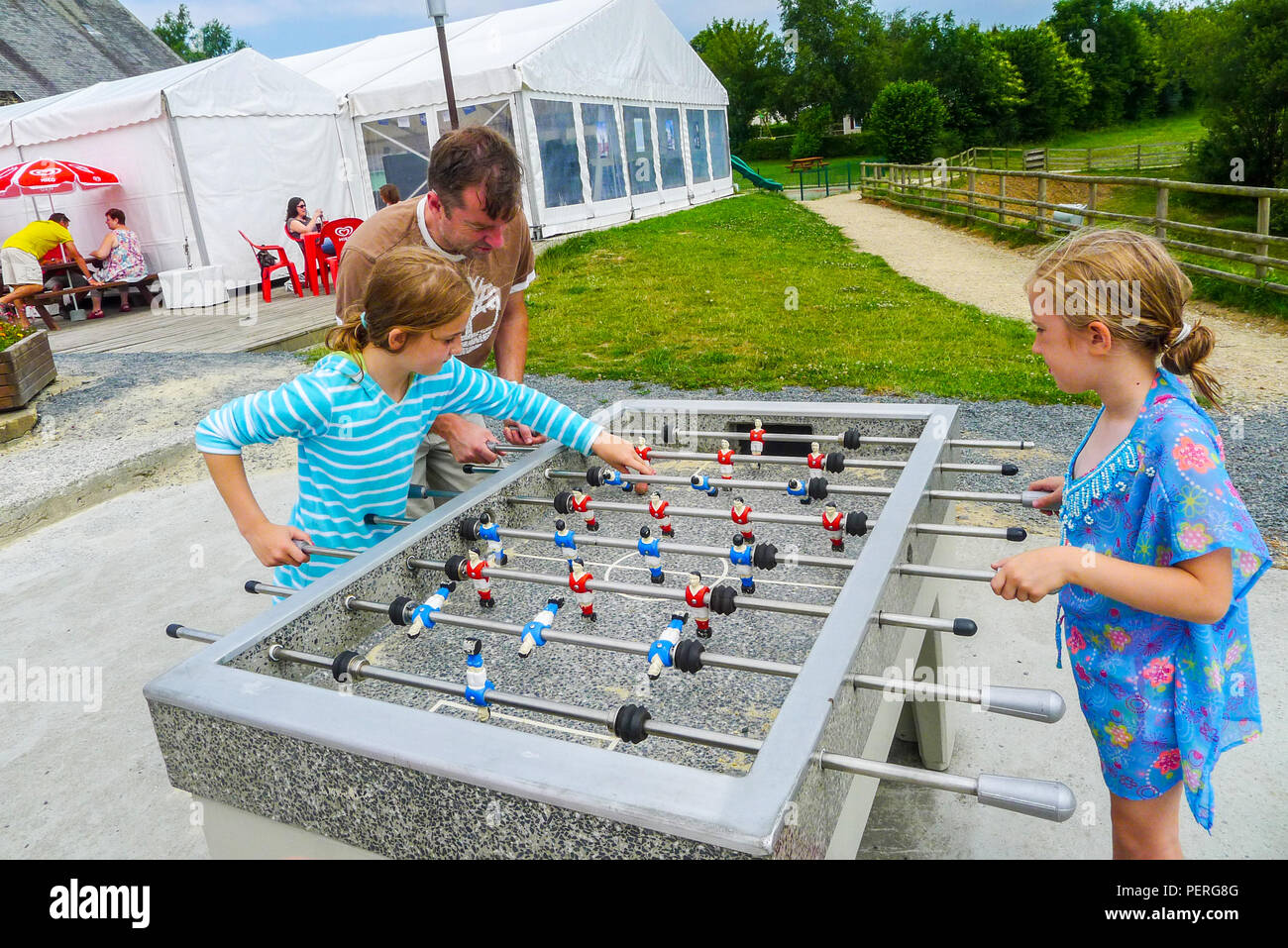 father and children playing table football/ Fussball / Fußball - Stock Image