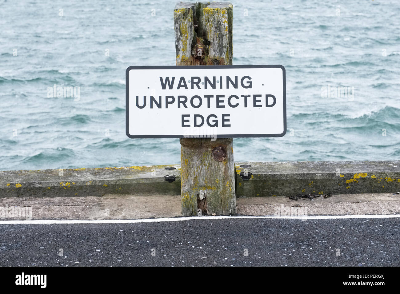 Unprotected edge warning sign at harbour port for car and vehicle safety preventing falling into the sea - Stock Image