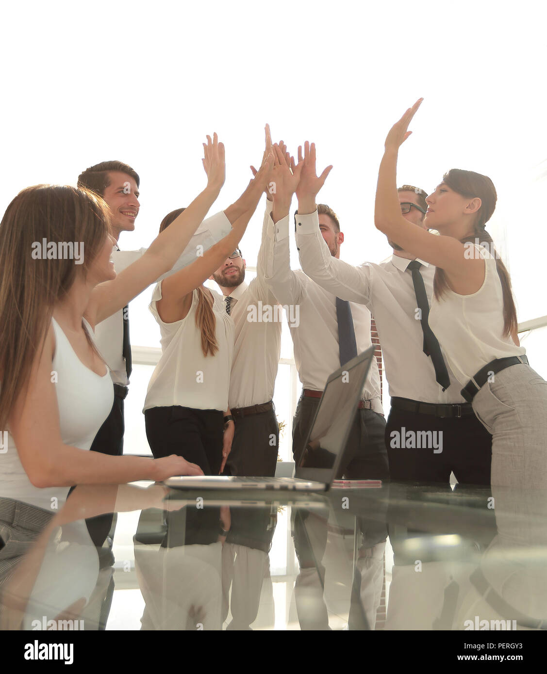 Portrait of a cheerful business team joining hands together in bright office - Stock Image