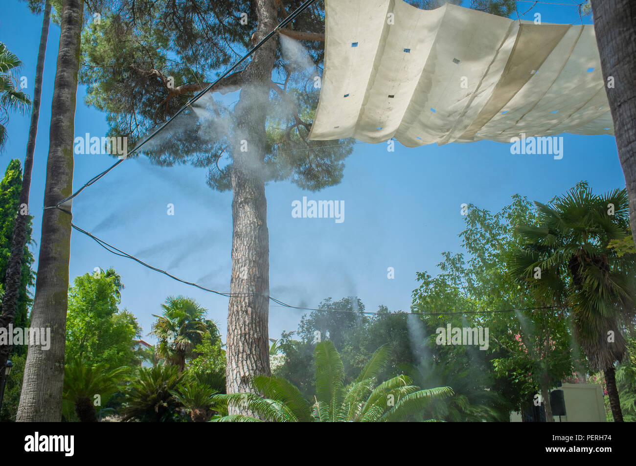 Awning and sprinklers splashing vaporized water at public park. Devices for cooling the hot summer temperature in Spain outdoors - Stock Image