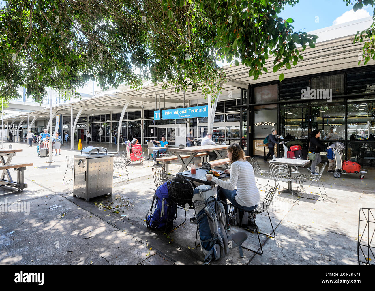 People seated at a café outside Sydney Airport International Terminal T1, New South Wales, NSW, Australia - Stock Image