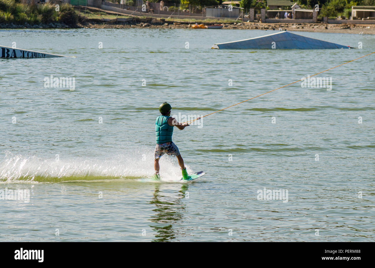 Teenage boy wakeboarding, skurfing, water skiing, on a lake, Wake Park, Pedro de Alcántara, Andalusia, Spain. - Stock Image