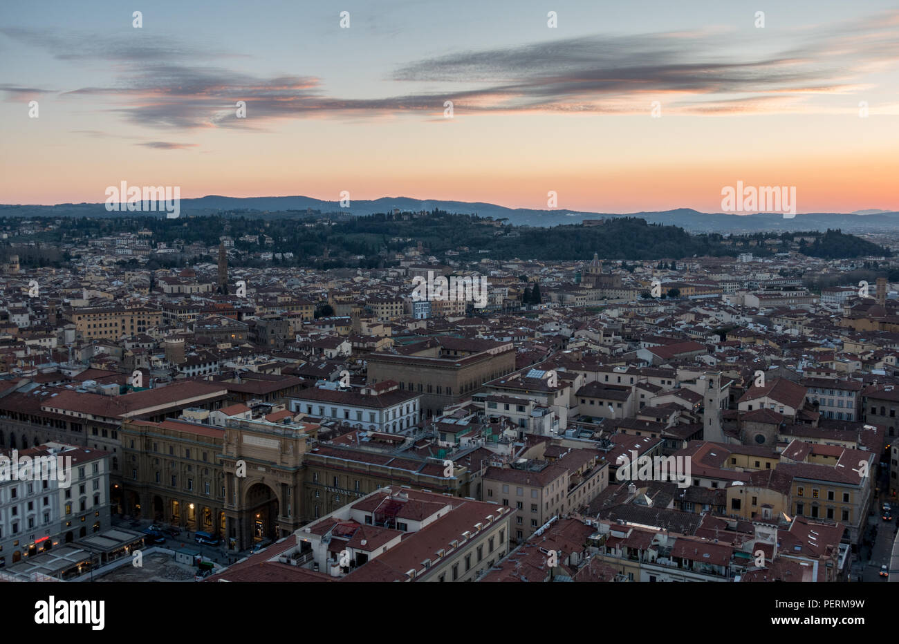 Florence, Italy - March 23, 2018: Evening illuminates the rooftops of Florence city, with the villa-topped hills of Bellosguardo rising behind. - Stock Image