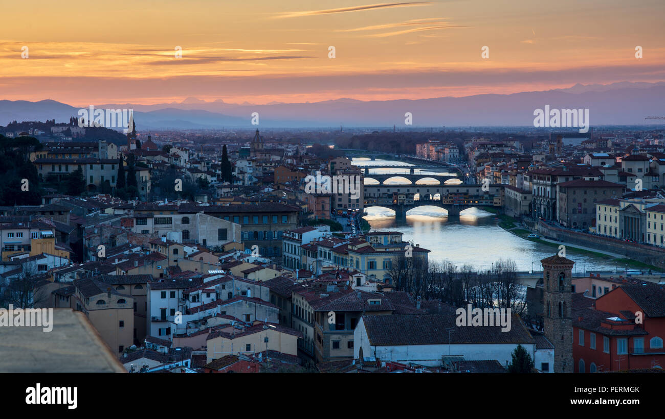 Florence, Italy - March 23, 2018: Evening light illuminates the cityscape of Florence along the Arno River, including the landmark Ponte Vecchio bridg - Stock Image