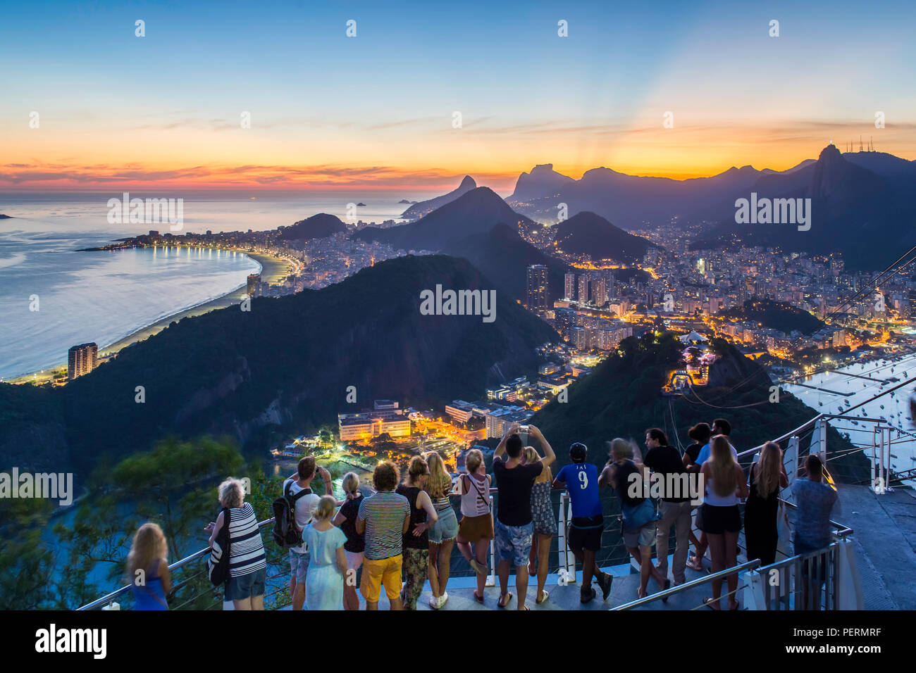 Tourists viewing Christ the Redeemer on Mount Corcovado and the city at sunset from Sugarloaf (Pao de Acucar) in Rio de Janeiro, Brazil Stock Photo
