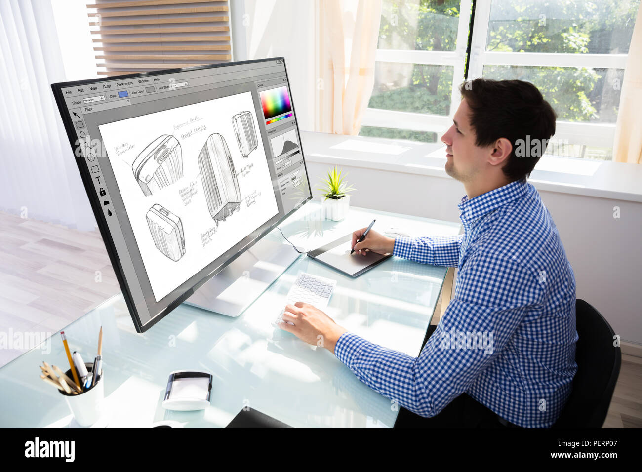 Side view of a young male Designer Drawing Suitcase On Computer Using Graphic Tablet - Stock Image
