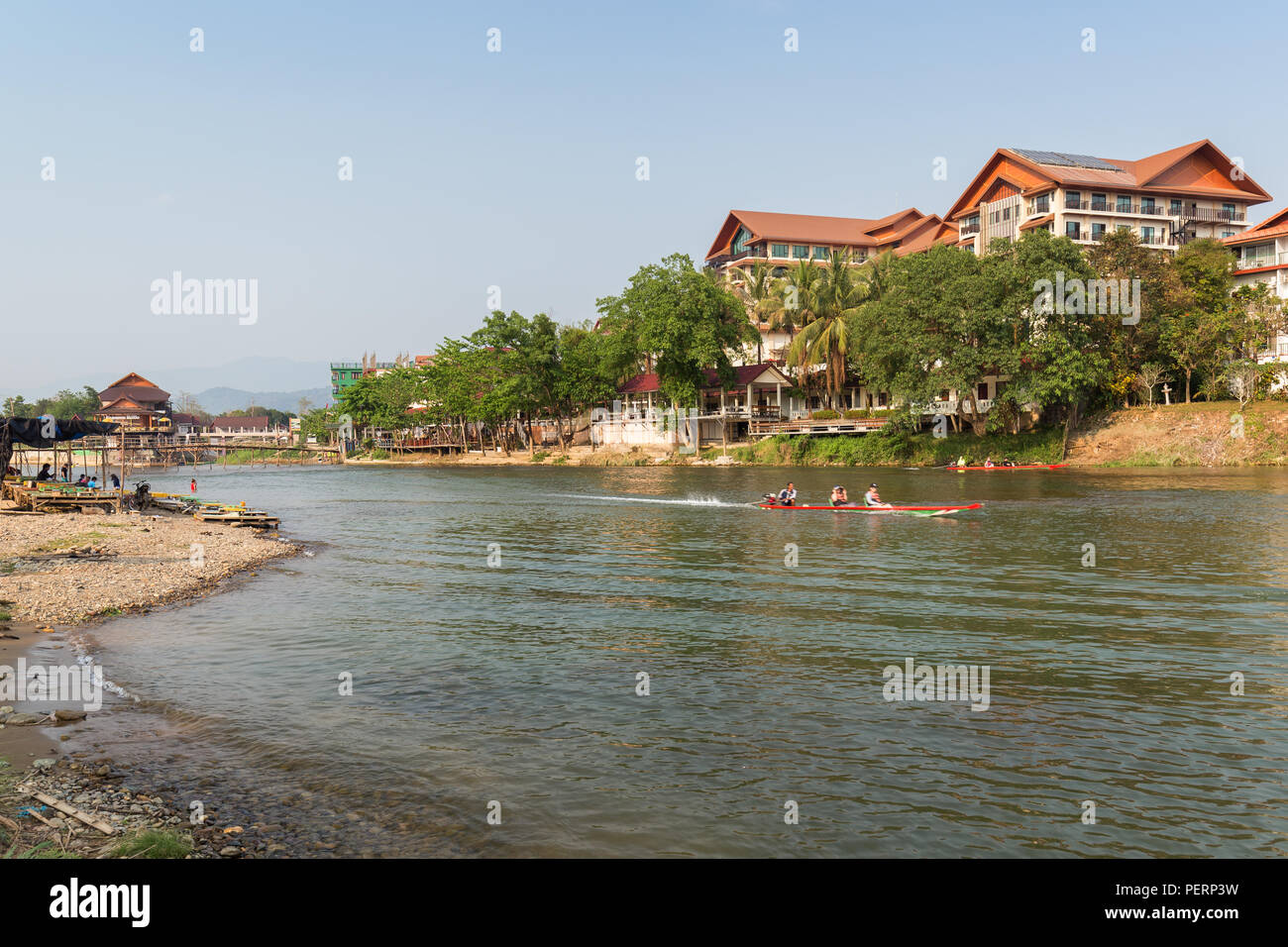 Few people and boats on the Nam Song River and hotels in Vang Vieng, Vientiane Province, Laos, on a sunny day. - Stock Image