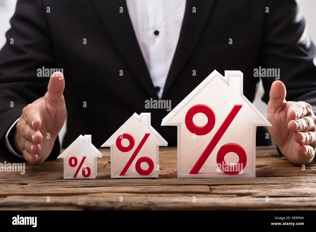 Close-up of a businessperson's hand protecting increasing house models with red percentage symbols - Stock Image