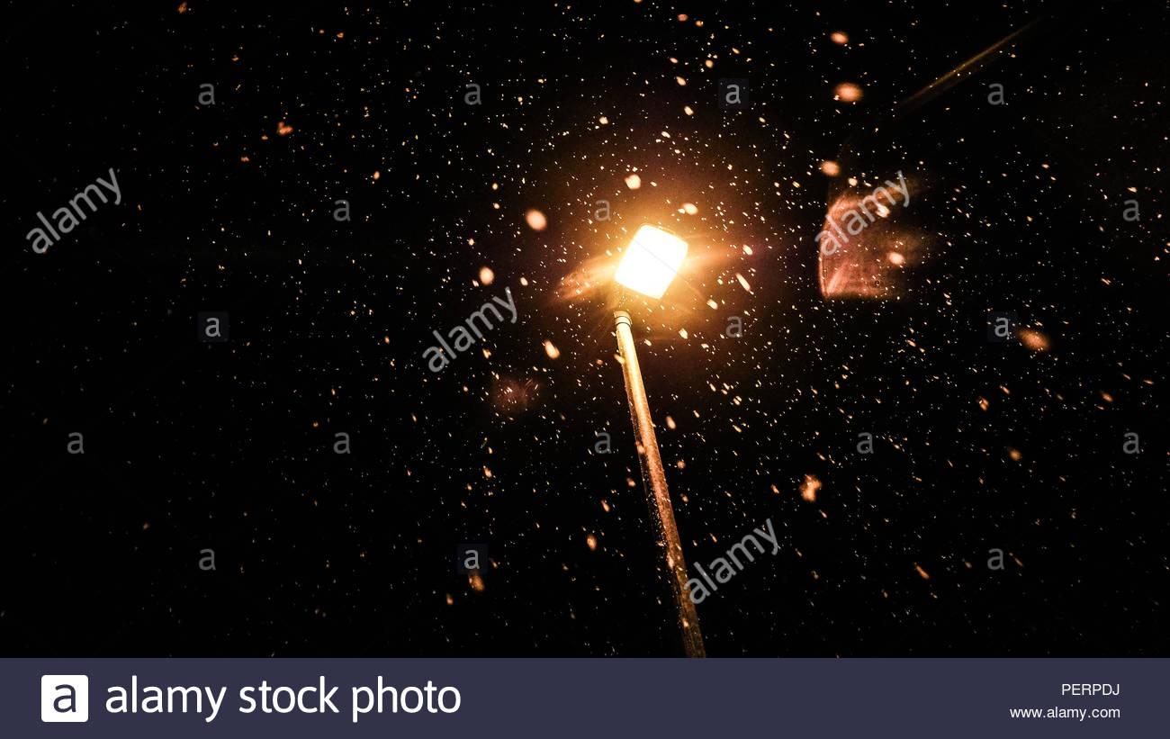 Snow light by a streetlamp at night - Stock Image