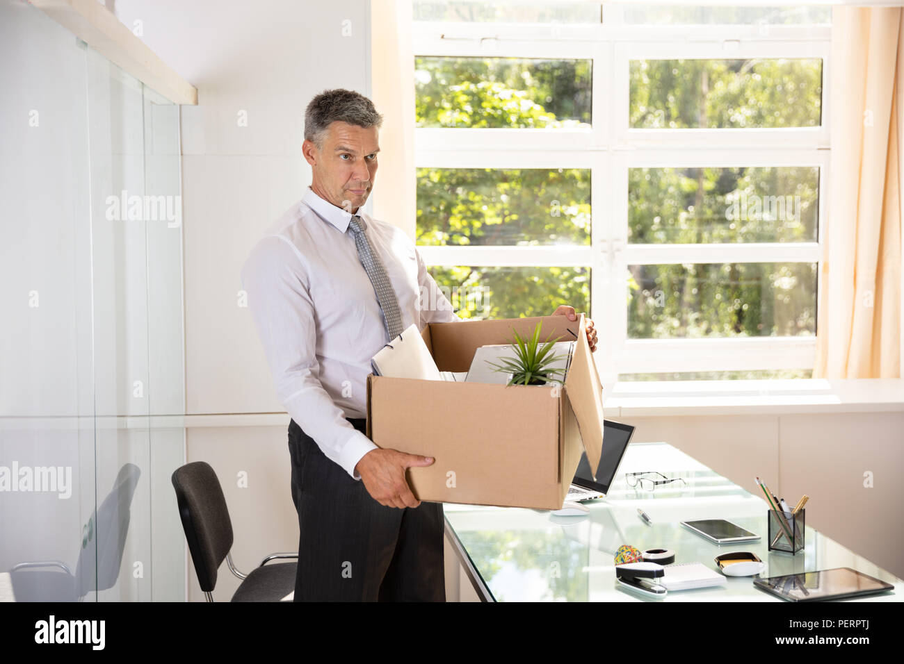 unhappy mature businessman carrying belongings in cardboard box at