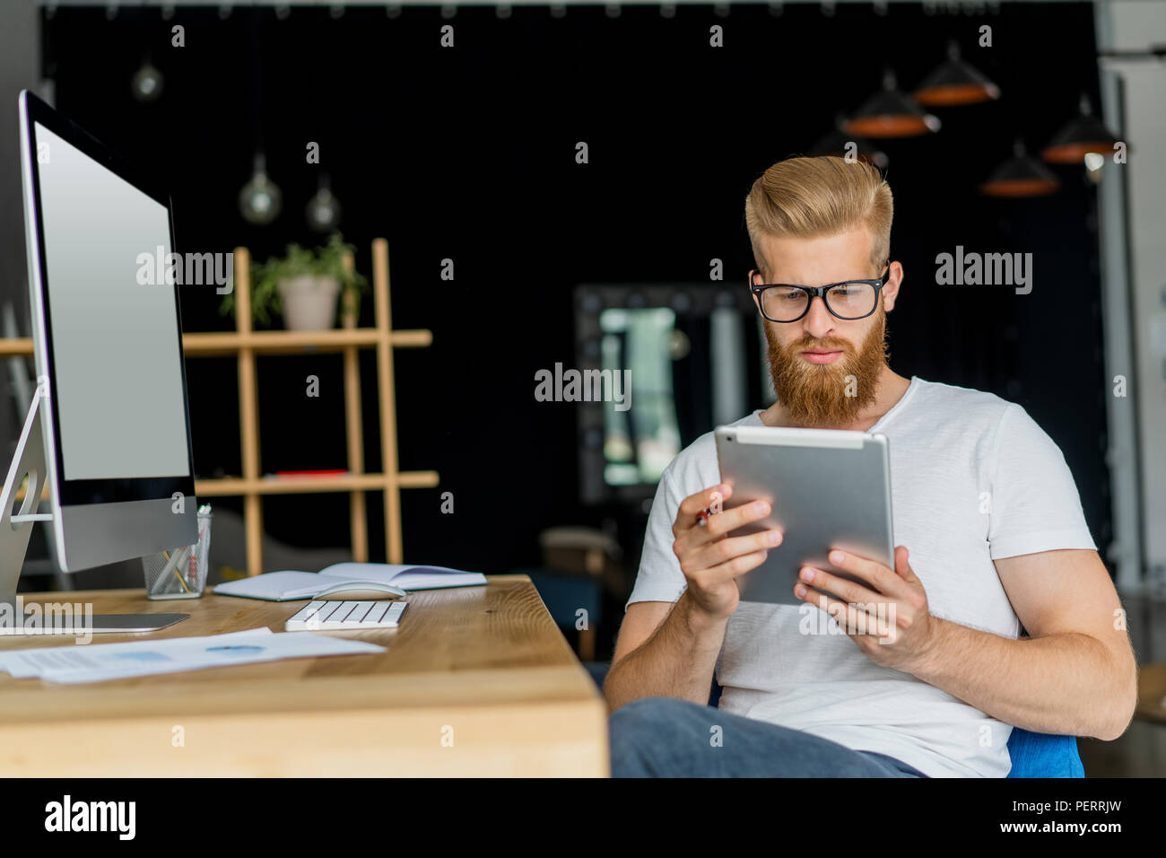 Multitasking. Handsome young man wearing glasses and working with touchpad while sitting on the couch in office - Stock Image