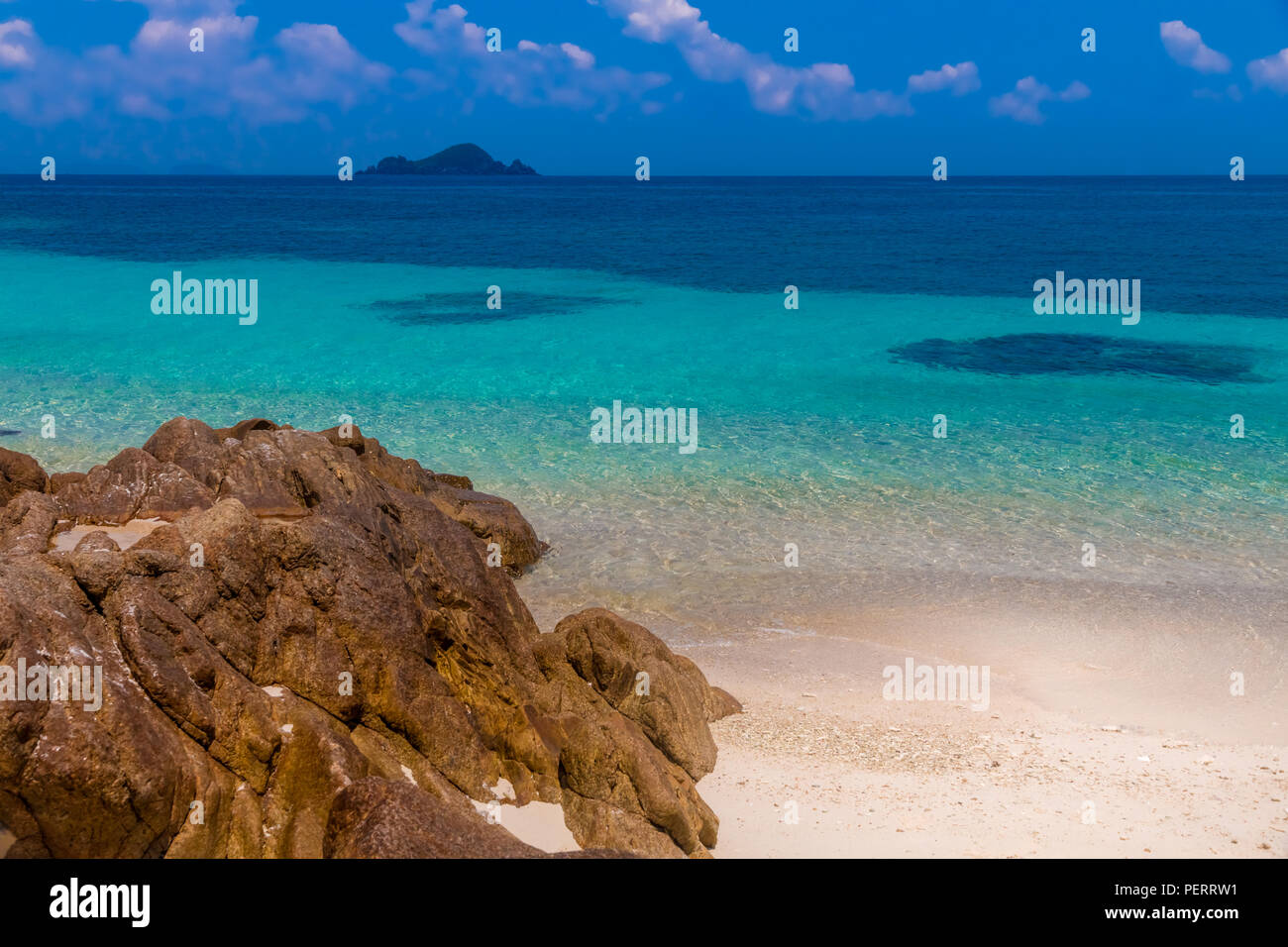 Beautiful scenery of the turquoise blue sea, the white powdery sand and the rock reaching out to the shallow clear water glimmering in front of Rawa... - Stock Image