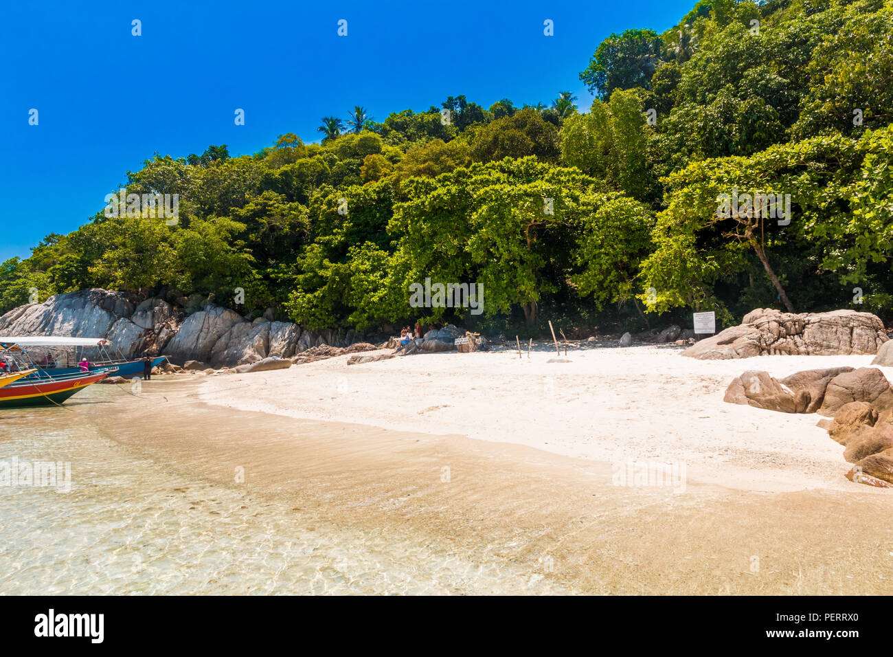 The powdery white sandy beach surrounded by rocks & trees, tourists resting in the shade and boats floating on the glimmering shallow water of... - Stock Image