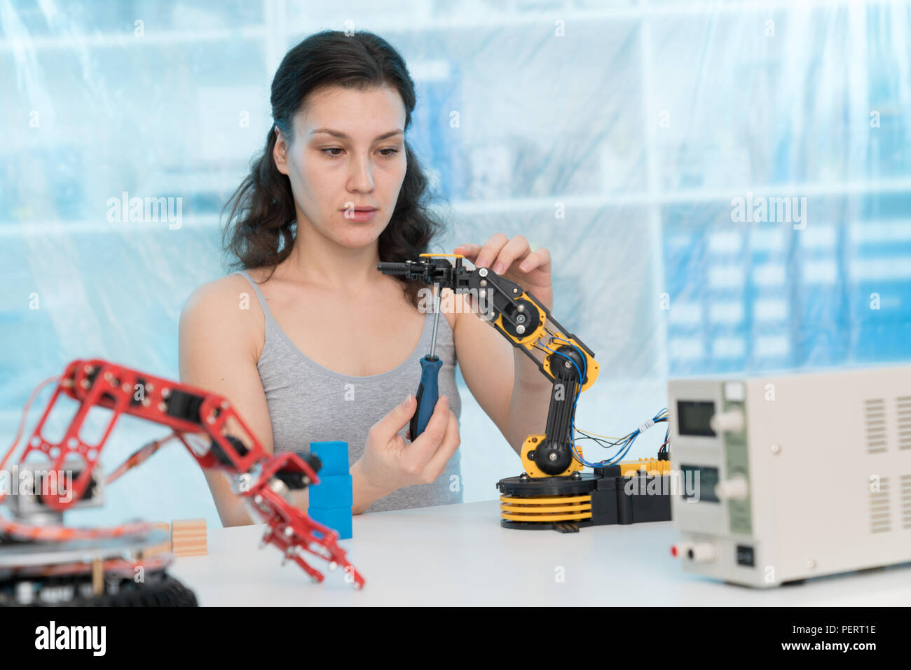 girl in a University laboratory is experimenting with a robot - Stock Image