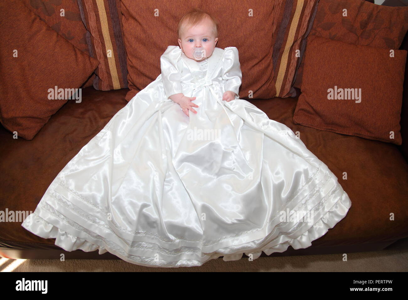 6 month old baby girl in her christening gown - Stock Image