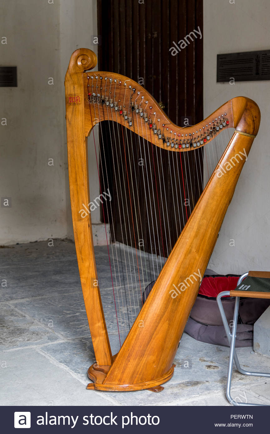 A Celtic or Irish Harp in a sideroom of the mostly ruined Kilfenora Cathedral, Co. Clare, Republic of Ireland ready to entertain a coach party. Stock Photo