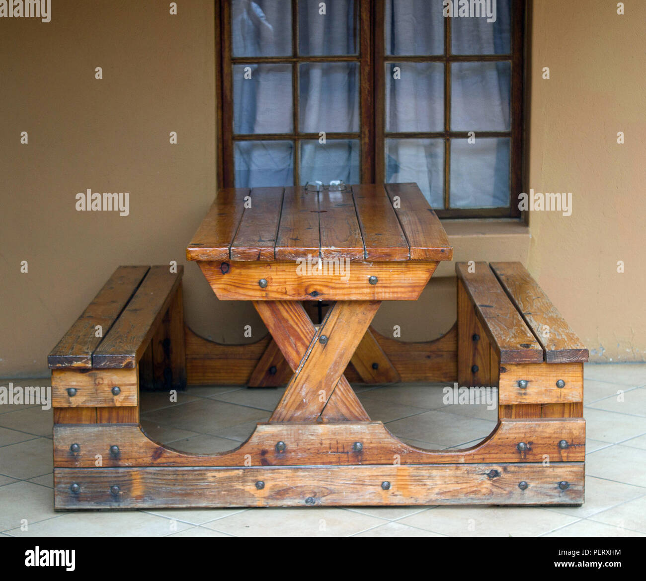 Sturdy wooden table with two seats attached as one unit standing on stoep against a window - Stock Image