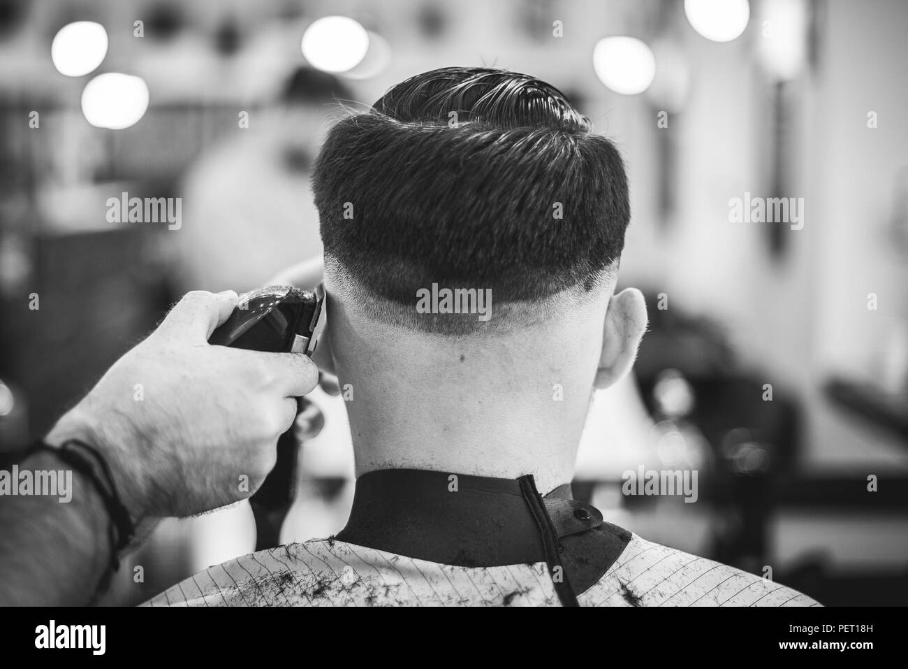 Man hairdresser doing hairstyle with hairdryer and comb a man with a beard - Stock Image