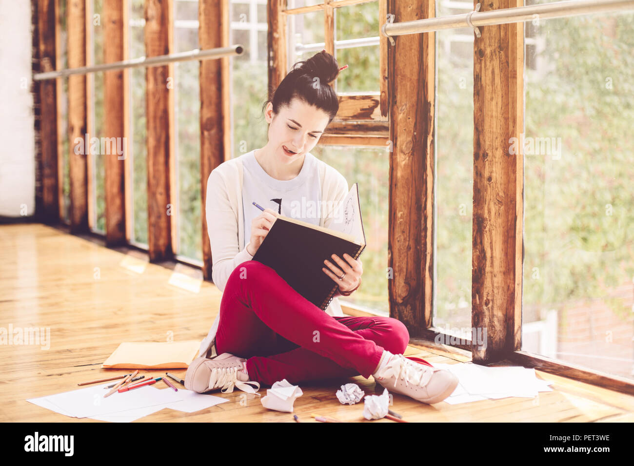 Portrait of beautiful smiling white caucasian young brunette woman student female artist sitting on floor in college university drawing sketching pe