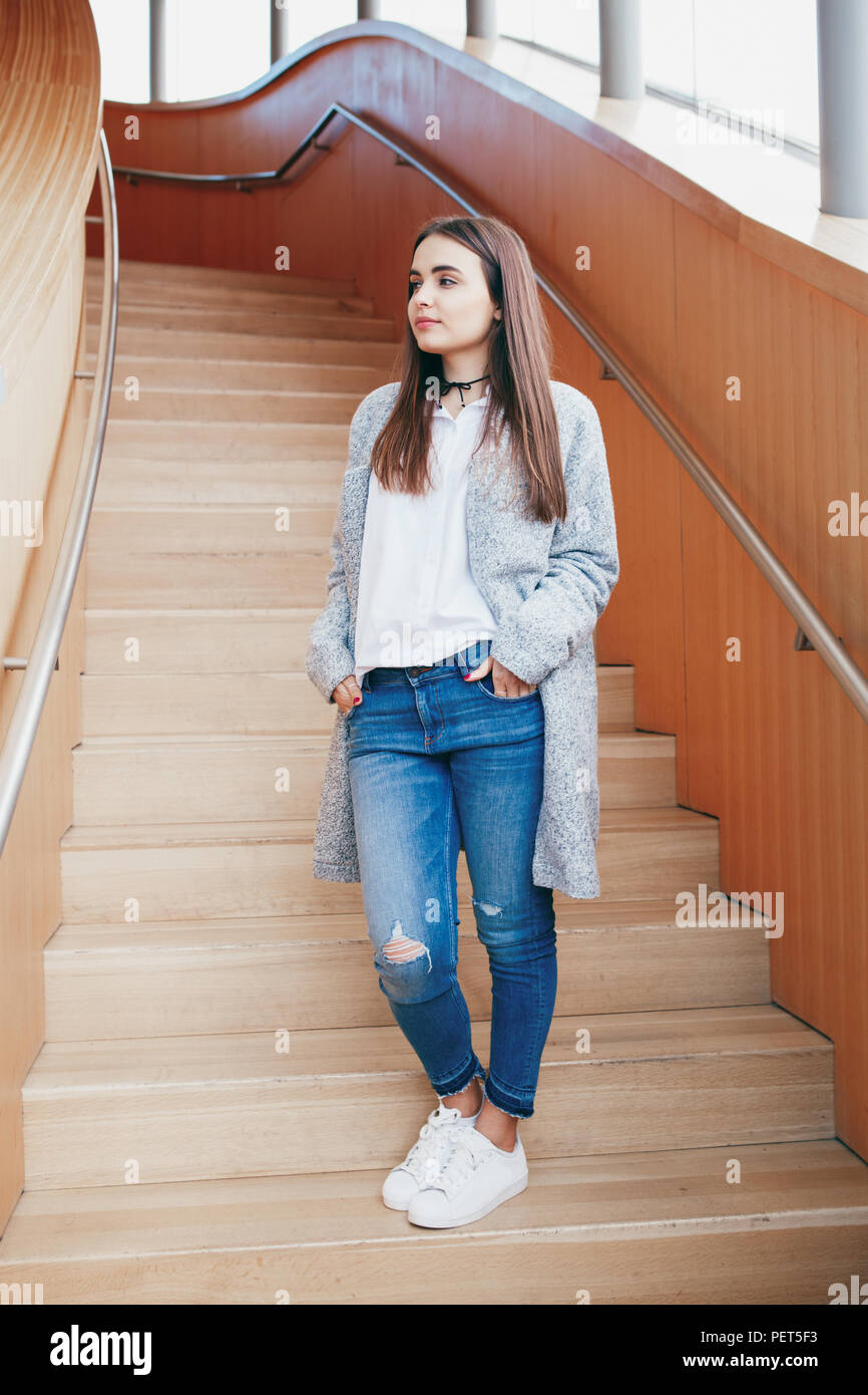 17702b5fac6 Portrait of young beautiful stylish young Caucasian girl woman student with  long brown hair in white shirt