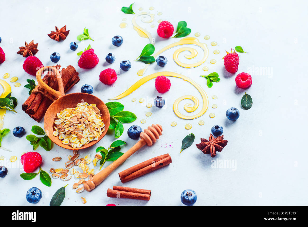 Healthy breakfast concept with oatmeal, honey, cinnamon, and berries on a white wooden background. Cooking porridge flat lay with copy space - Stock Image