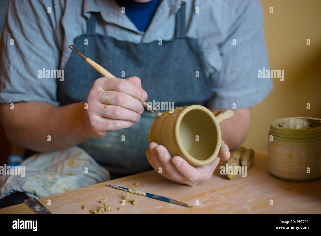 Professional potter making pattern on clay mug with special tool in