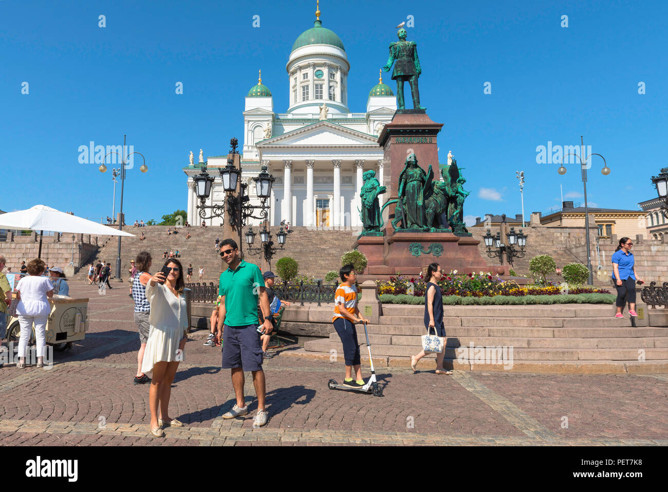 Finland tourism summer, view of a tourist couple in Helsinki posing for a selfie photo in front of the Lutheran Cathedral and Alexander Monument. - Stock Image