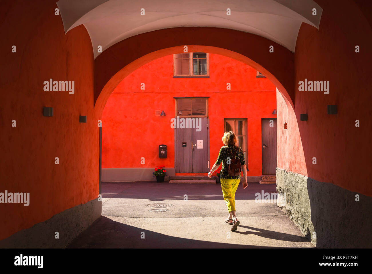 Woman solo travel, rear view of a middle aged female traveller walking alone through a colorful arcade in the old town quarter of Helsinski, Finland. - Stock Image