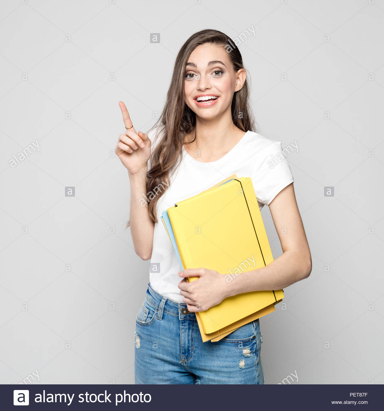 Studio portrait of happy young woman wearing white t-shirt and jeans holding yellow files and pointing with index finger. Grey background. - Stock Image
