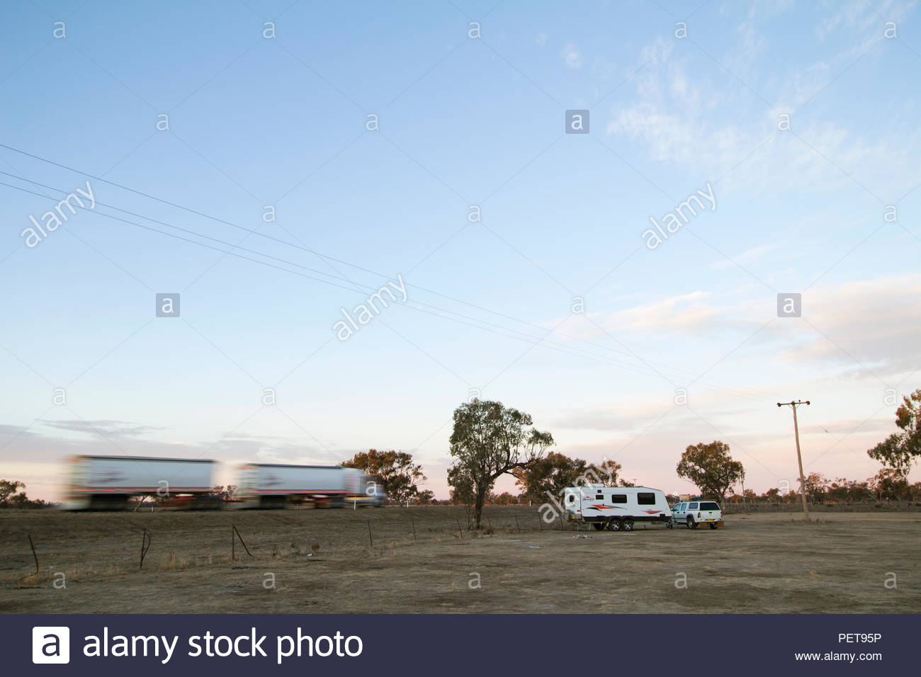 A heavy road truck drives past a camp site in the Australian outback. While free or low cost campgrounds are popular with caravaners they are often cl - Stock Image