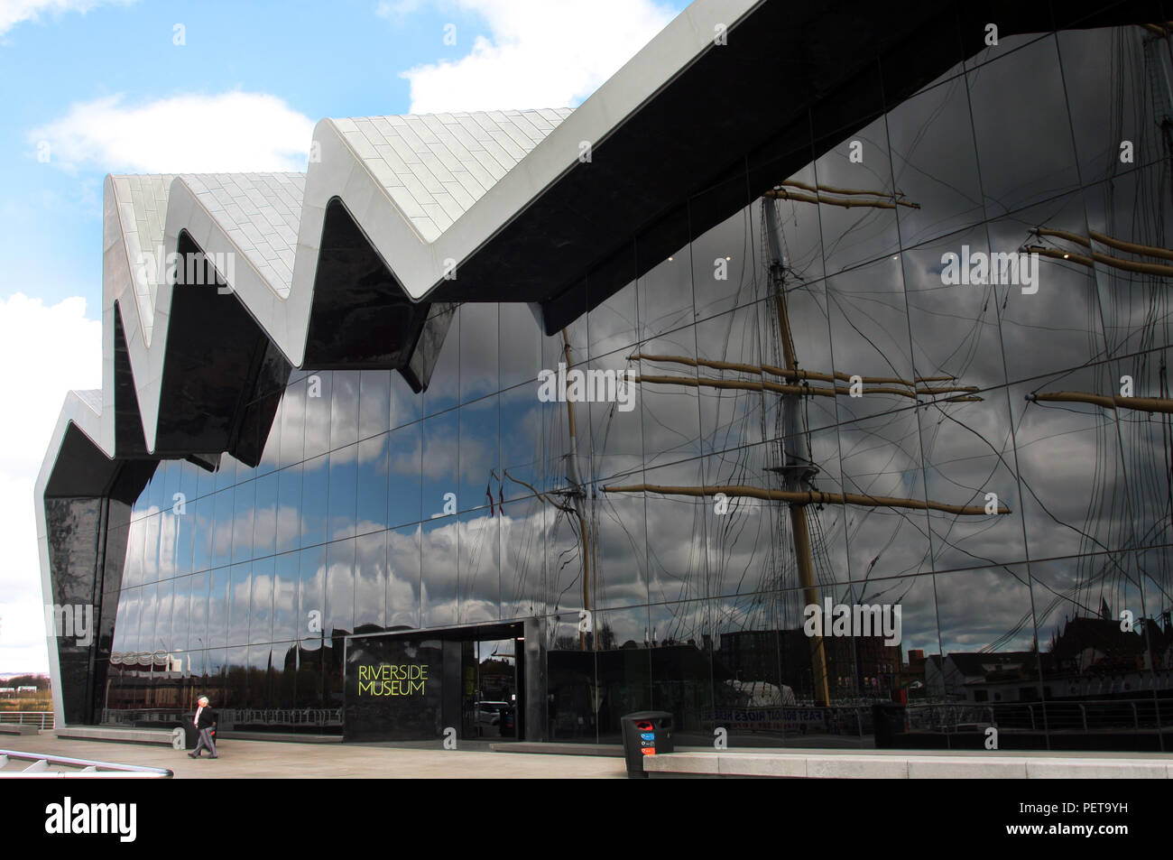 The dramatic front of the Riverside Museum which sits on the banks of the River Clyde. It is Glasgow's transport museum and was designed by Zaha Hadid. It is an extremely popular museum that attracts many tourists and visitors every year. The tall ship, The Glenlee, which was built on the Clyde and is moored at the museum, is reflected in the windows of the museum. Stock Photo