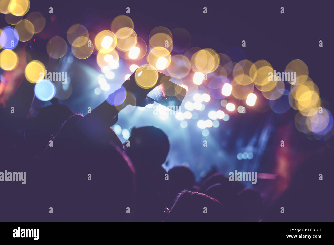 Silhouettes of festival concert crowd in front of bright stage lights. - Stock Image