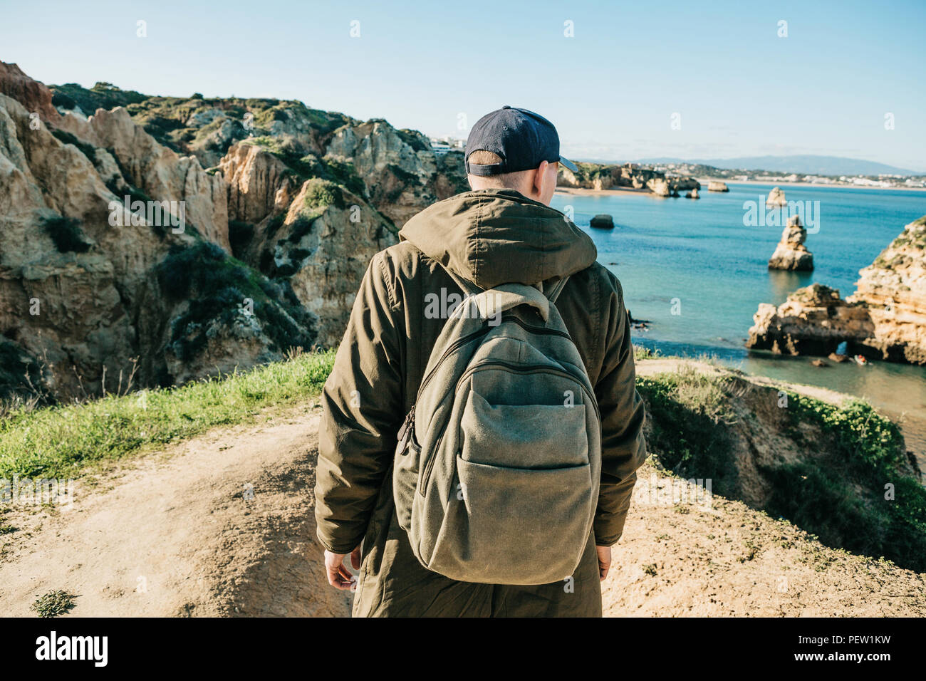 A tourist or traveler with a backpack admires the beautiful view of the  Atlantic Ocean and the coast near the city called Lagos in Portugal. d4532e20a5f82