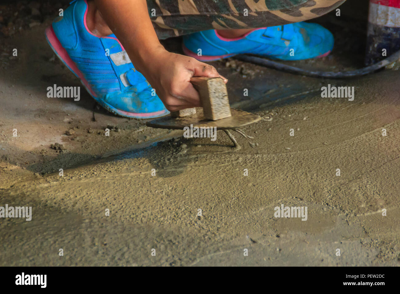 Mason worker use trowel to smooth or leveling liquid concrete of flooring work in step of the building improvement. Stock Photo