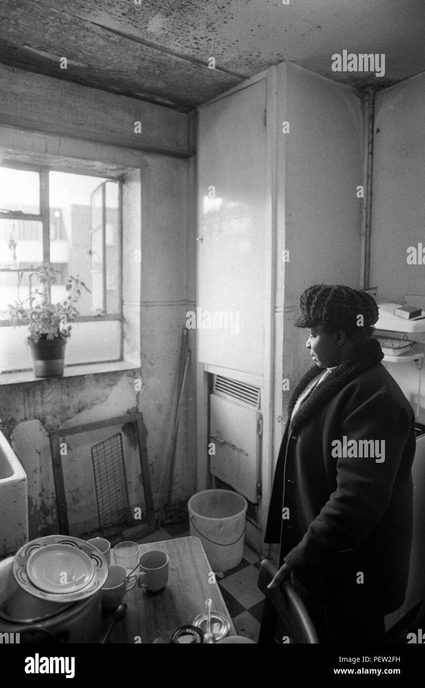 1970s poverty UK. Elderly oap black woman in her council estate flat. London. England She is very upset about the amount of damp that is coming into her kitchen. HOMER SYKES - Stock Image