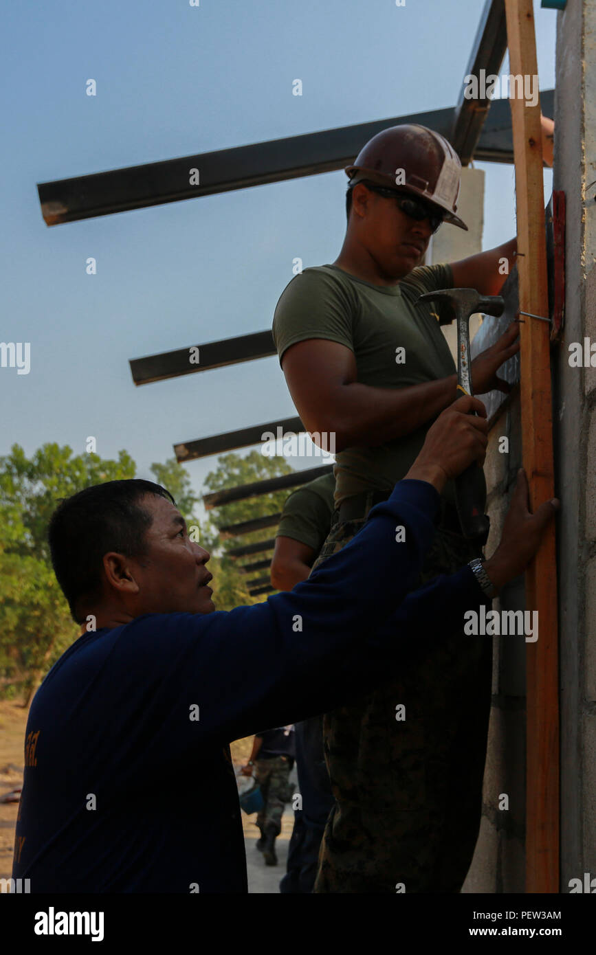 A member of the Royal Thai Navy lays (left) helps U.S. Marine Corps Cpl. Jacob Colvin (right), combat engineer, with Marine Wing Support Squadron 171, hammer a wooden plank during the building of a multi-purpose room for the Banchamkho school during exercise Cobra Gold 2016 in Rayong, Kingdom of Thailand, Jan. 30, 2016. Cobra Gold 2016, in its 35th iteration, includes a specific focus on Humanitarian Civic Action, community engagement, and medical activities conducted during the exercise to support the needs and humanitarian interests of civilian populations around the region. (U.S. Marine Cor - Stock Image