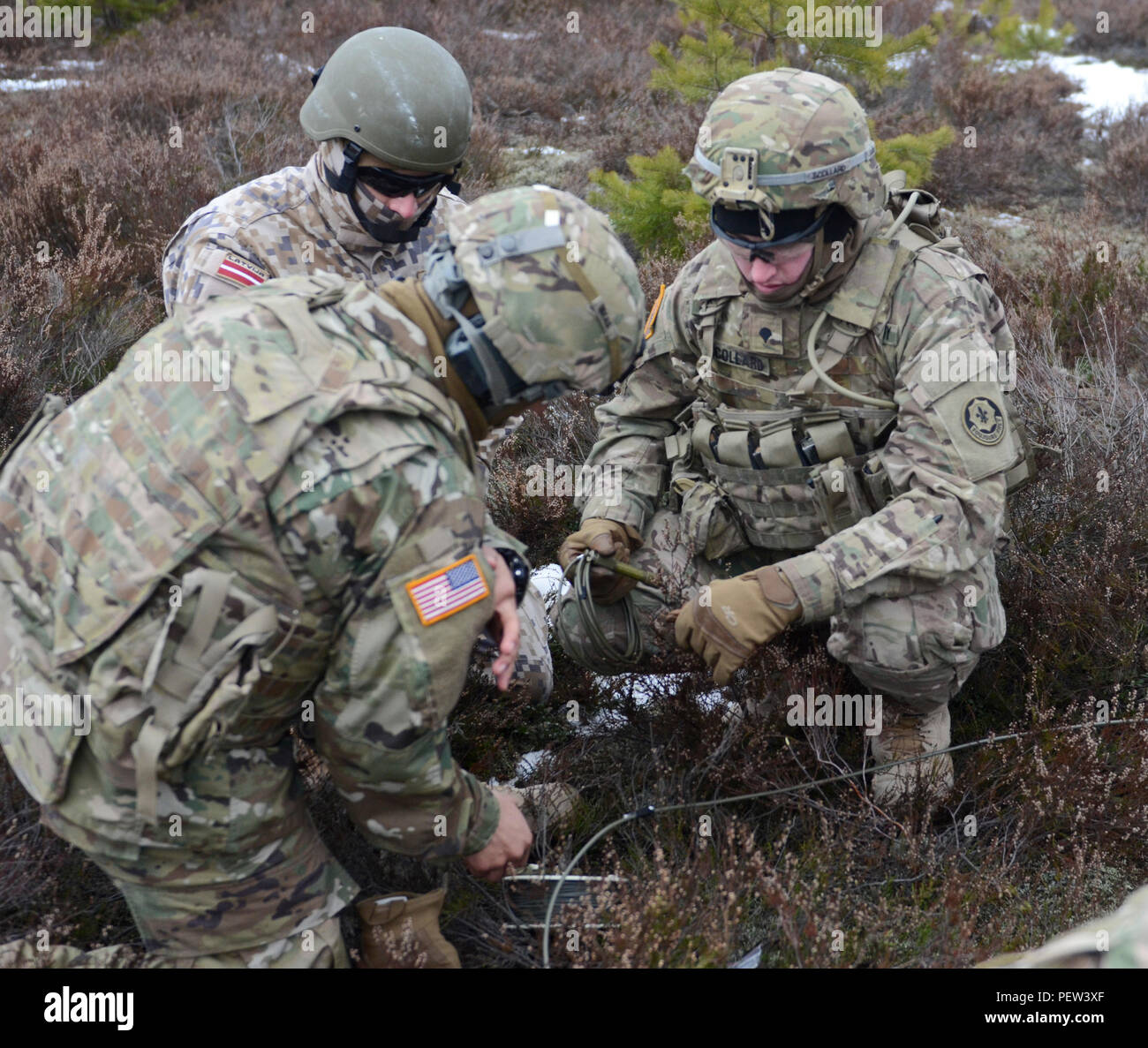 Soldiers of 3rd Squadron, 2nd Cavalry Regiment, stationed out of Vilseck, Germany, along with a Latvian Engineer Soldier, prepare to connect the fuse lines to the improvised explosive devices during a demolition exercise at Adazi Training Area in Latvia, Jan. 29, 2016. (Photo by Staff Sgt. Steven Colvin/Released) - Stock Image