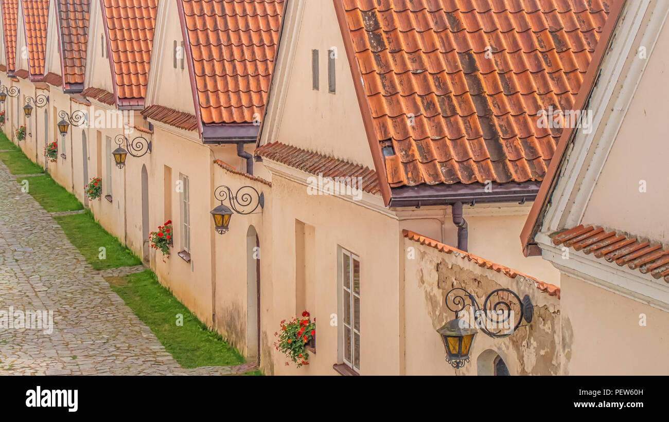 Row of country houses with a tiled roof and flowers on the windows - Stock Image