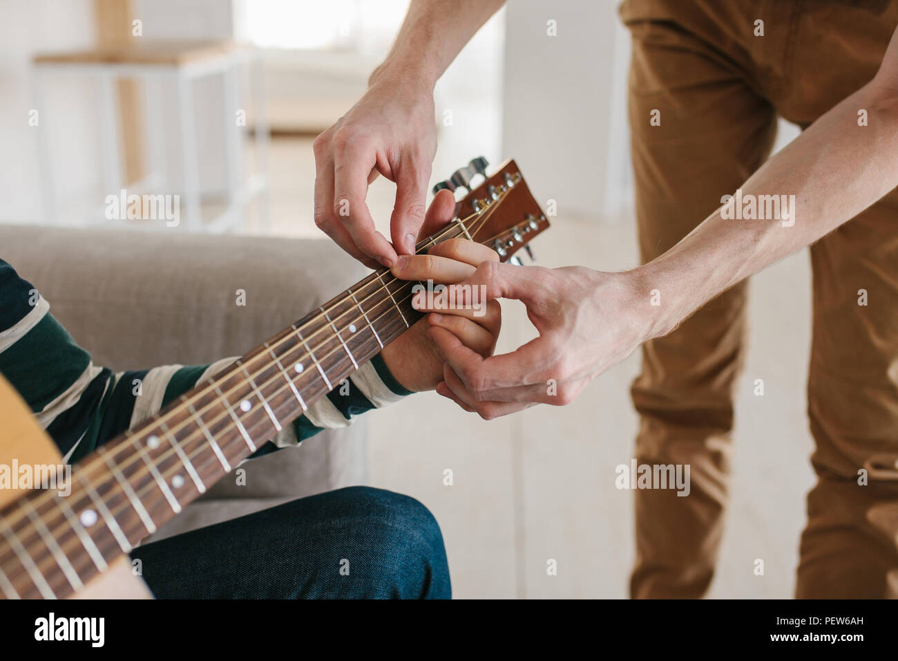 Learning to play the guitar. Music education and extracurricular lessons. - Stock Image