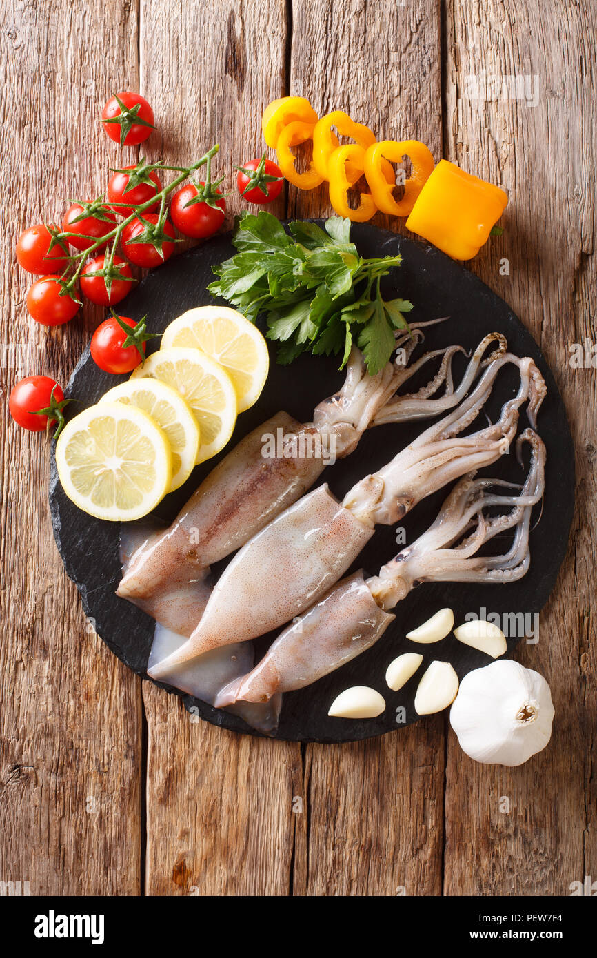Raw fresh squid close-up and vegetable for cooking on a slate board on a table. Vertical top view from above - Stock Image