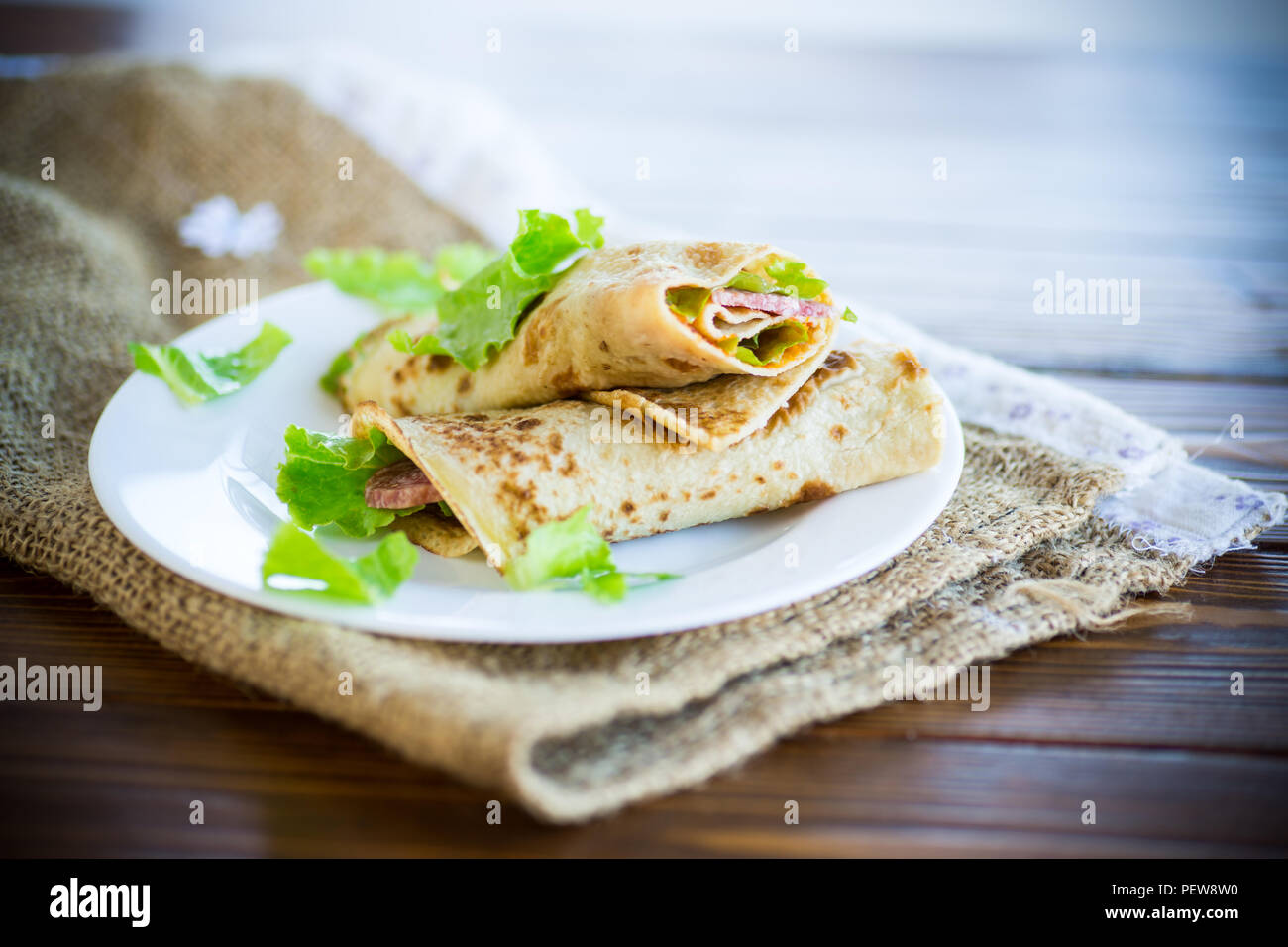 thin pancakes with salad leaves and bacon in a plate on a wooden table - Stock Image