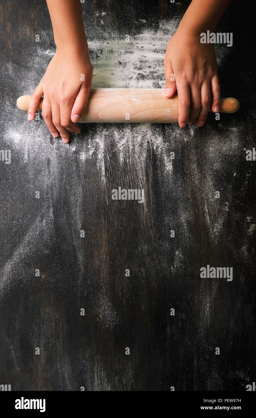 Girl hands keep rolling pin with flour on dark black table, baking background, top view, copy space for your text, meru, recipe. Banner Stock Photo