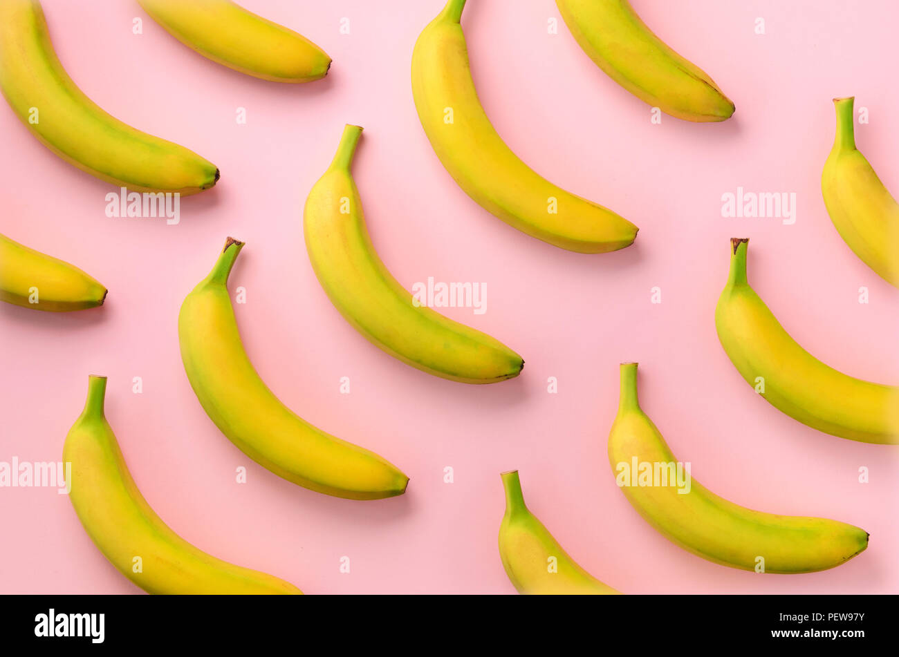 Colorful fruit pattern. Bananas over pink background. Top view. Pop art design, creative summer concept. Minimal flat lay style - Stock Image