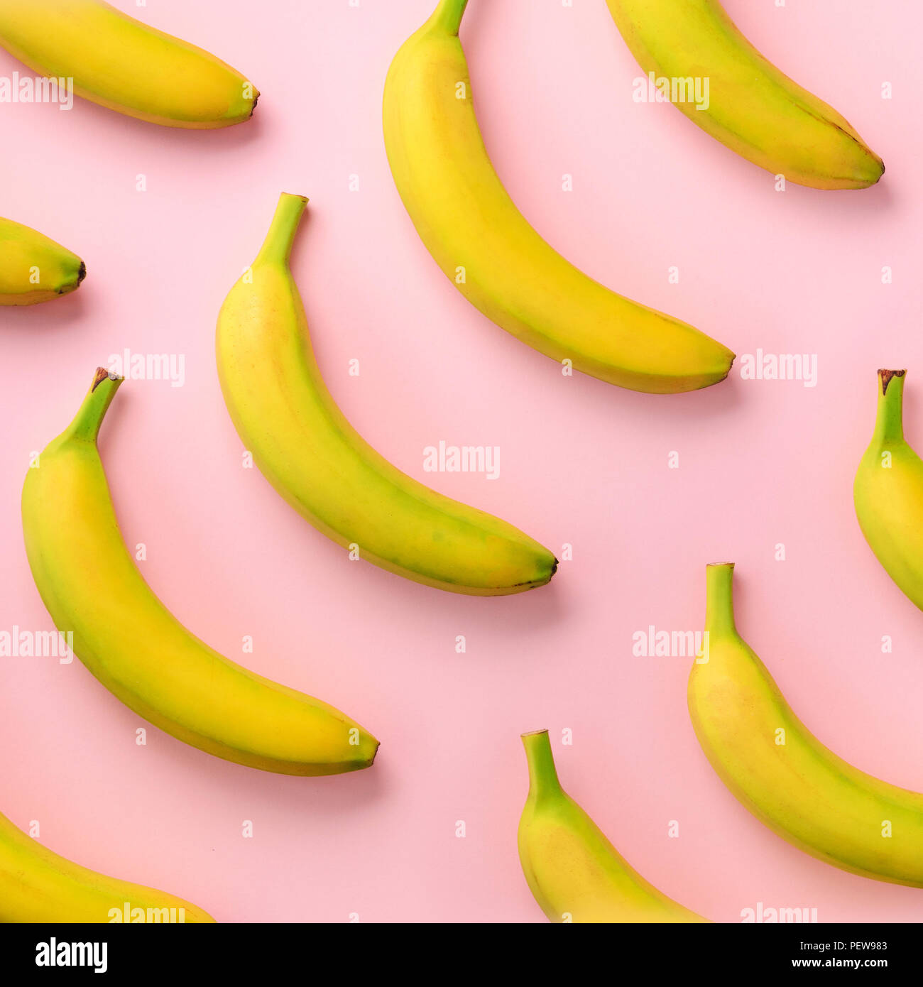 Colorful fruit pattern. Bananas over pink background. Square crop. Top view. Pop art design, creative summer concept. Minimal flat lay style - Stock Image