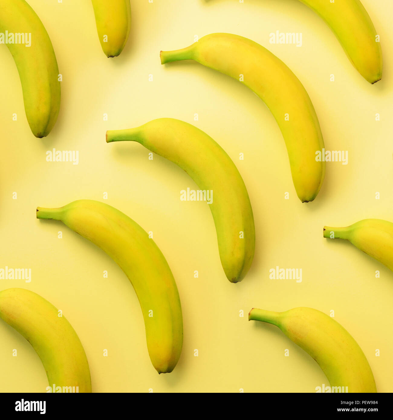 Colorful fruit pattern. Bananas over yellow background. Square crop. Top view. Pop art design, creative summer concept. Minimal flat lay style - Stock Image