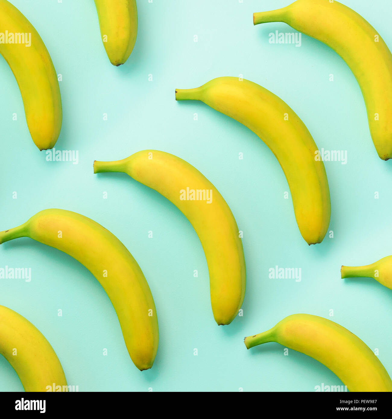 Colorful fruit pattern. Bananas over blue background. Square crop. Top view. Pop art design, creative summer concept. Minimal flat lay style - Stock Image
