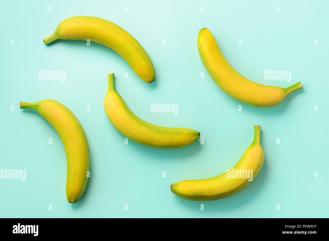 Colorful fruit pattern. Bananas over blue background. Top view. Pop art design, creative summer concept. Minimal flat lay style - Stock Image