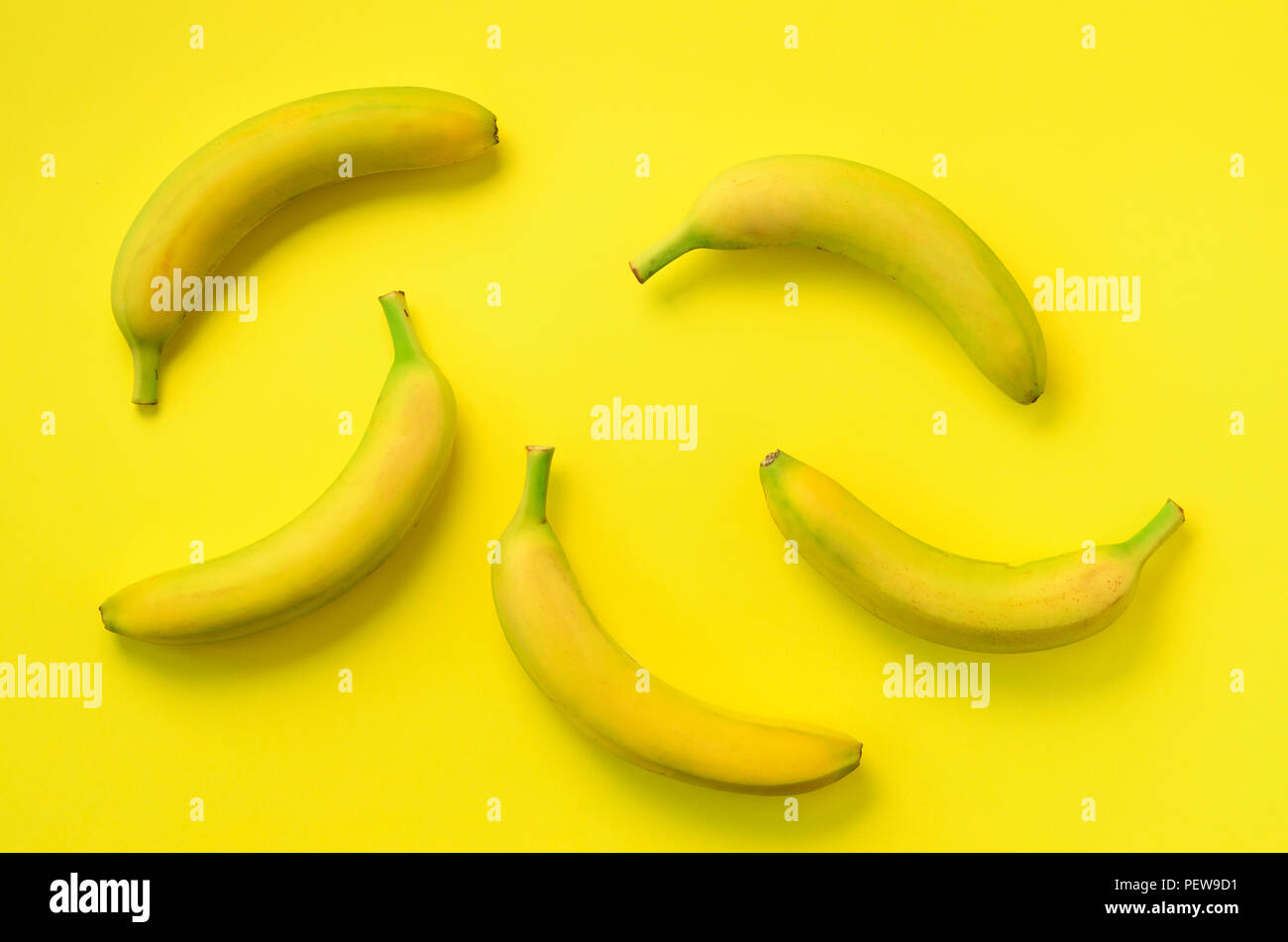 Colorful fruit pattern. Bananas over yellow background. Top view. Pop art design, creative summer concept. Minimal flat lay style - Stock Image
